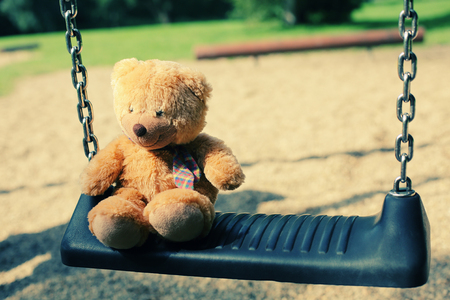 Bear doll sitting on the swing in the park
