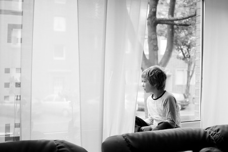 8 year old: 8 year old boy sitting near the window and looking to the street Stock Photo