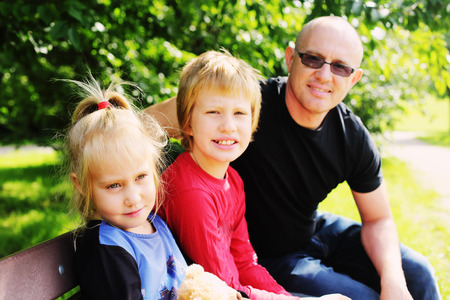 Portrait of father with two kids outdoors photo
