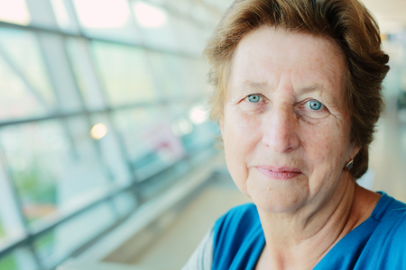 Portrait of beautiful 70 years old woman sitting in the airport Stock Photo