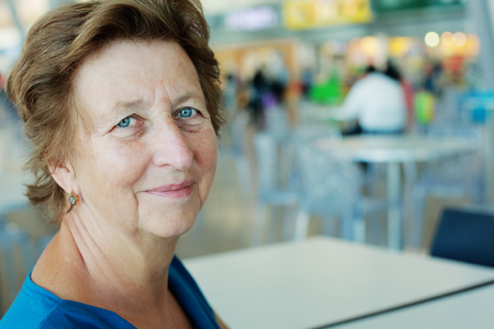 the sixties: Portrait of beautiful 70 years old woman sitting in the indoor cafe
