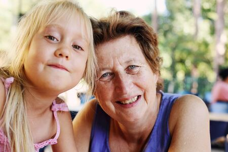 Portrait of beautiful 70 years old woman with 5 years old granddaughter