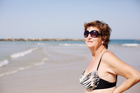 Senior woman standing on the beach