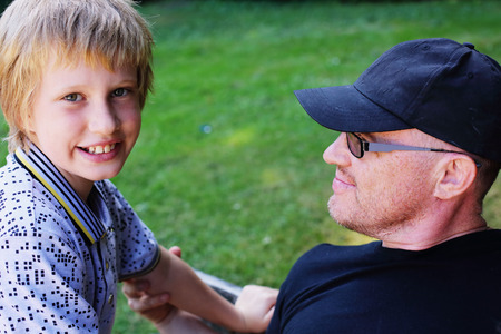 nine years old: Portrait of father and son outdoors