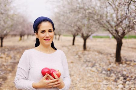 赤いリンゴを保持している 40 歳女性の屋外のポートレート 写真素材 - 75270039
