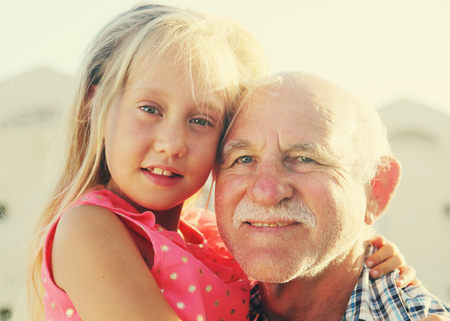 70s: grandfather holding 6 years old granddaughter Stock Photo