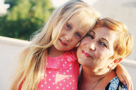 Portrait of grandmother with 6 years old granddaughter Stock Photo
