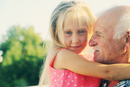 grandfather holding 6 years old granddaughter Stock Photo