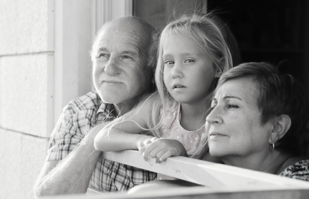 grandfather and grandmother holding 6 years old granddaughter photo