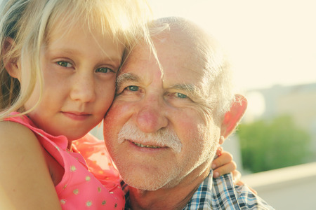 grandfather holding 6 years old granddaughter photo