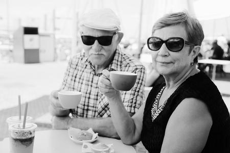 Portrait of senior couple sitting in summer cafe photo