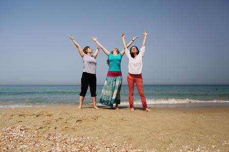Portrait of three beautiful 40 years old women walking on seaside