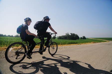 father and son ride a tandem bike Stock Photo