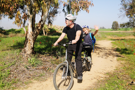 father with autistic 10 years old son ride a tandem bike