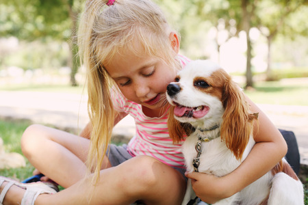 7 year old girl is walking with a puppy in the park Stock Photo