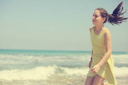 12 years old girl teen girl in yellow dress walking on seaside. Summer vacation