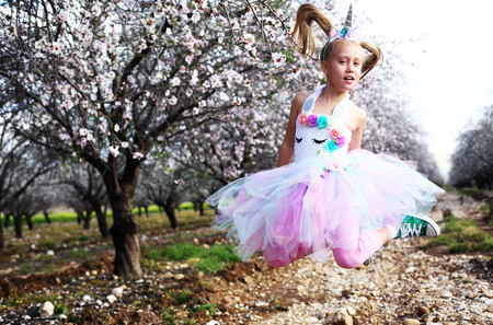 Girl in a unicorn costume jumps outdoors. Spring is around, apple trees are blooming.