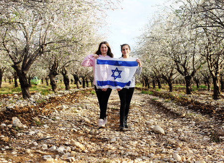 Two teenage girls are holding an Israeli flag outdoors Stock fotó