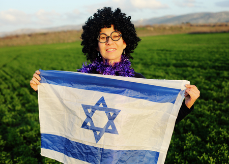 woman in a black wig holding the flag of Israel