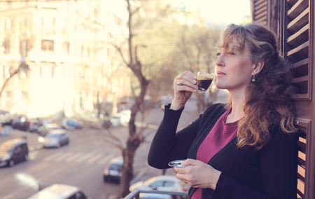 beautiful mature woman standing on the balcony looking to the street Stock fotó