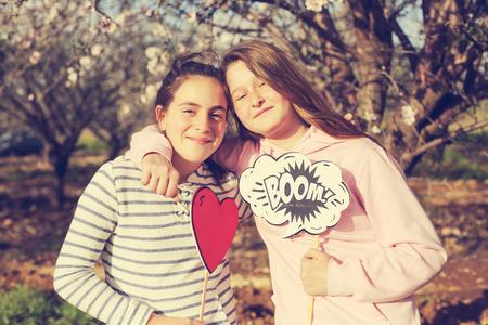 Two teenage girlfriends  holding boom! shape and heart shape