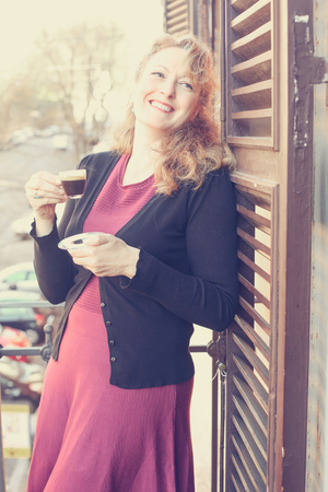Beautiful mature woman standing on the balcony, holding a cup of coffee Imagens