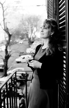 Beautiful mature woman standing on the balcony with coffee looking at the street Stock fotó
