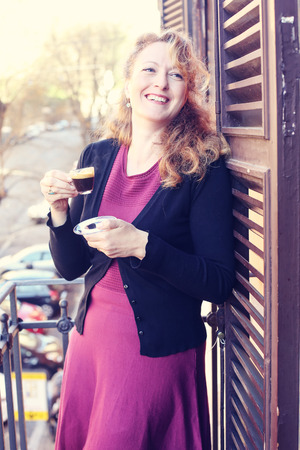 Beautiful mature woman standing on the balcony, smiling with a cup of coffee Stock fotó