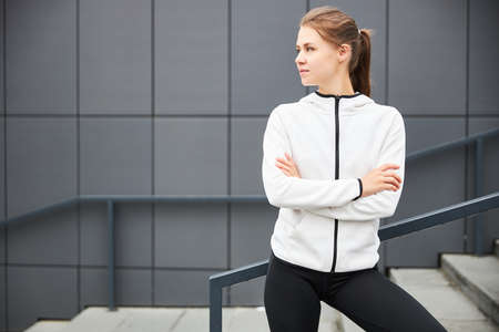 Young smiling female resting after an active fitness training while standing against gray wall with copy space area for your text message, satisfied fit woman resting after an active fitness training