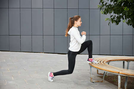 A young girl trains on the street. Grey metal background. Cityscape. Empty space for your text. 写真素材