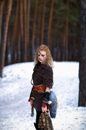Blonde Viking woman holds animal tails from hunting