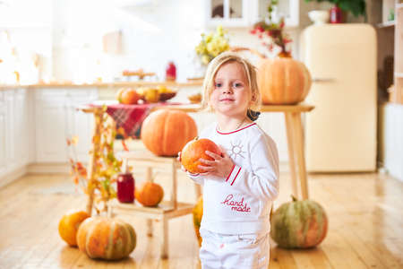 A little blonde girl sits on a wooden floor in a white kitchen next to a large orange autumn pumpkin