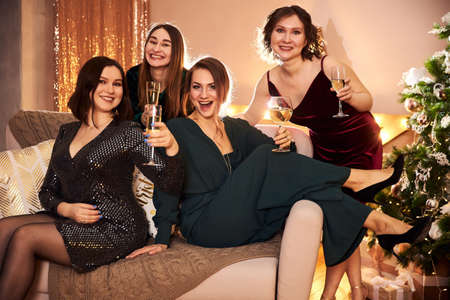 Four beautiful women celebrate the new year or Christmas in beautiful evening dresses in a decorated for the holiday room with garlands and gifts drink at the party
