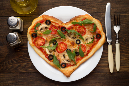 pepperbox: Tasty hot pizza in heart shape with chicken and mushrooms and cutlery on wooden table. Fresh italian dish for Valentines day. Top view. Stock Photo