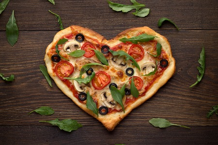 scattered in heart shaped: Tasty italian heart shaped pizza with chicken, mushrooms and scattered arugulas leaves on wooden rustic background. Mediterranean dish for romantic dinner on Valentines day. Top view. Stock Photo