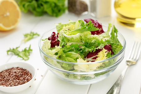 Mixed salad of iceberg, radiccio, endive, cabbage with flax seeds, oil and lemon on white wooden background for healthy diet.