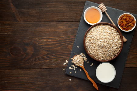 Oat flakes in the bowl and honey, raisins, milk on slate board and rustic wooden background. Oats bowl top view, copy space. Stock Photo
