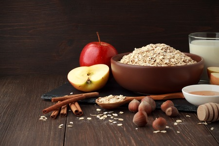Still life of ingredients for healthy diet: oat flakes in bowl with apple, cinnamon, nuts, honey, milk on wooden table. Concept of healthy food. Copy space.