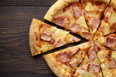 Sliced hawaiian pizza with ham and pineapple on dark wooden table. Top view, copy space, closeup.