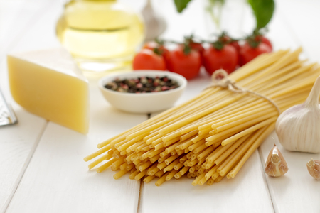cooking oil: Dry pasta with cheese, tomatoes, garlic, oil and basil on white wooden background. Stock Photo