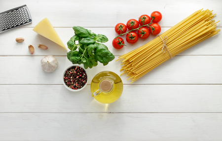 cooking oil: Culinary background with raw ingredients for pasta recipe on white wooden background. Dry bucatini or spaghetti with fresh tomatoes, basil and cheese. Top view, copy space. Stock Photo