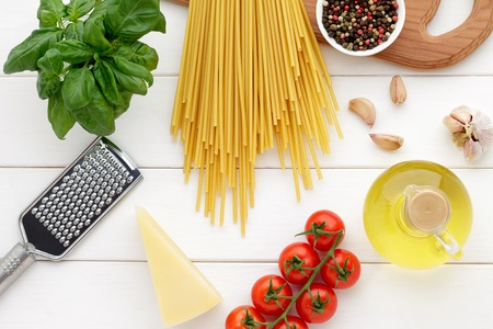 cooking oil: Italian pasta bucatini with tomatoes, basil, oil, garlic and cheese on white wooden table. Culinary background with ingredients for cooking healthy food. Top view. Stock Photo