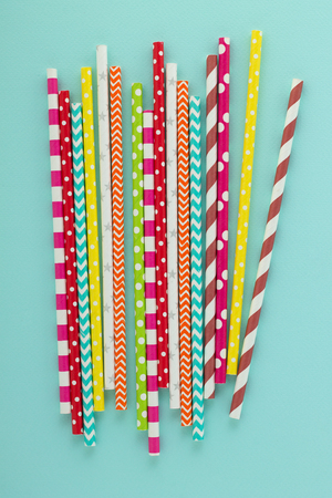 Drinking disposable straws for beverage on cyan background. Multicolored party supplies on the table. Top view.