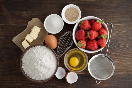 Ingredients for recipe of strawberry cake or pie on dark wooden background. Products ready to cooking homemade berry pastry. Top view.