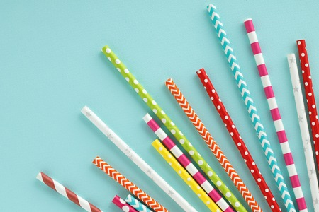 Colorful paper drinking straws on blue background. Flat lay with copy space. Stock Photo