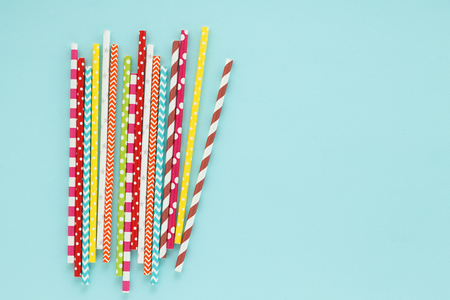 Multicolored drinking straws on cyan background. Event and party supplies, top view with copy space. Stock Photo