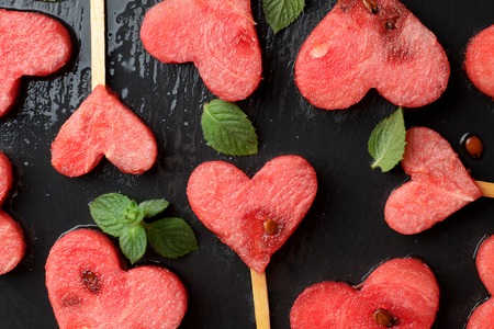 Watermelon hearts with mint on slate background. Love concept for Valentines day. Top view, closeup.