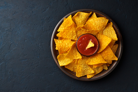 Nachos with dip sauce in a plate on dark stone blue background. Top view with copy space.