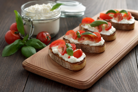 Homemade bruschetta with cheese feta, tomatoes and basil on cutting board. Italian snacks for lunch on wooden table.