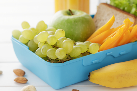 Lunch box with healthy snacks on white wooden background. Plastic container with sandwich, fruits and nuts closeup.